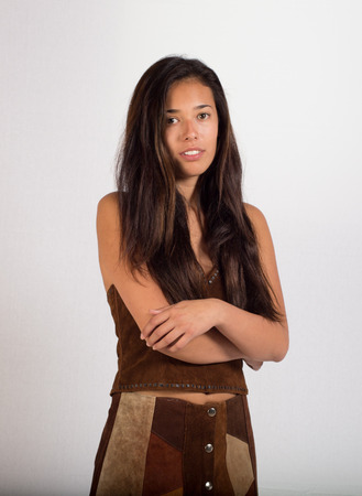 A pretty young lady posing in a suede outfit. This young woman looks like she could be Native American. photo