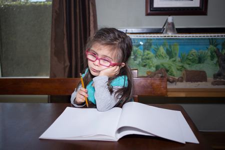 A cute little girl sitting at a table in front of a blank book and holding a pencil and thinking about what to write.