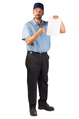 A blue collar worker standing, facing at an angle, holding a blank document that could be an invoice or a bill.