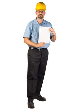 A blue collar worker wearing glasses, standing, facing at an angle, holding a blank document that could be an invoice or a bill.
