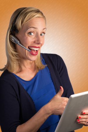 A blonde customer service lady is on the phone and appears to be very pleased with who she is talking to.