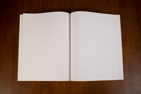 Blank white paper book or magazine in the open position that could be used to  that could be used to insert your own content for design purposes