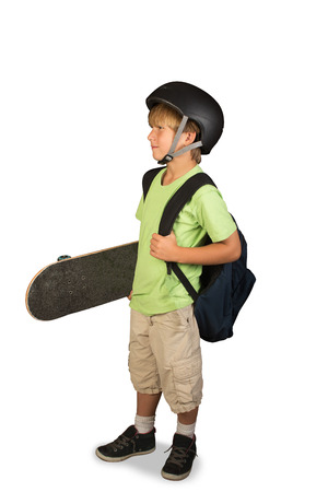 A young boy standing with a skateboard under his arm, carrying his backpack