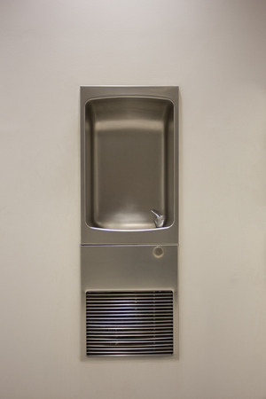 A beautifully crafted stainless steel drinking fountain is mounted into the wall of an indoor facility