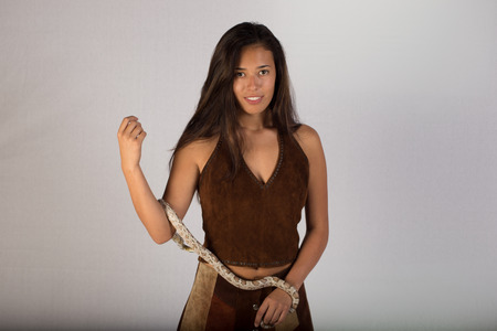 A pretty young lady posing in a suede outfit  This young woman looks like she could be Native American