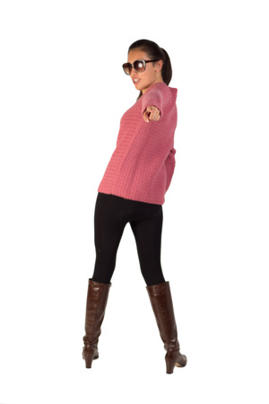 A young lady in casual attire pointing at the camera  She has high heel boots on as well as sunglasses