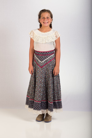 A young lady wearing western wear, including boots, skirt and blouse
