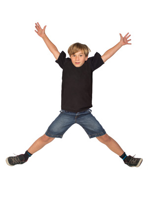 A young boy jumps in the air with hands and feet spread out like an X