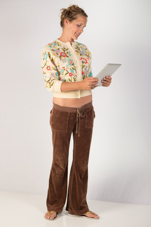 A pretty young lady holding a tablet device  She could be using the tablet to interact with to communicate or play a game online