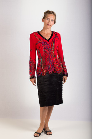 An atractive woman posing in an elegant red blouse and black skirt