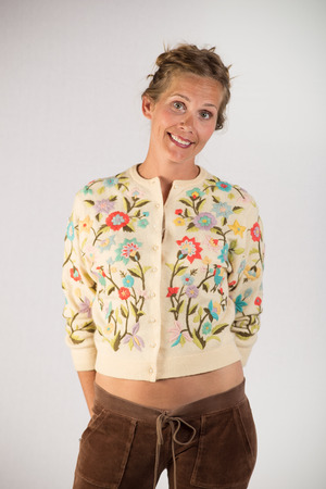 A elegant young lady posing for camera  Her hands are behind her back and is facing the camera  She is wearing flip flops, floral sweater with exposed waist, velvet brown pants   - Waist High Shot From the Front