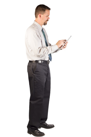 A white collar worker standing and using an iPad tablet  This man could be a corporate person that could  Stock Photo
