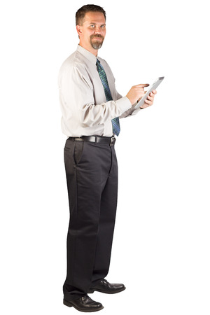 A white collar man standing and using a tablet device while looking at the camera
