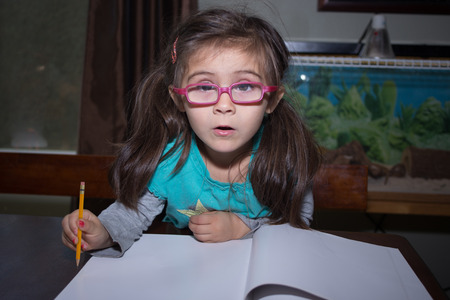 A cute little girl sitting at a table in front of a blank book and holding a pencil