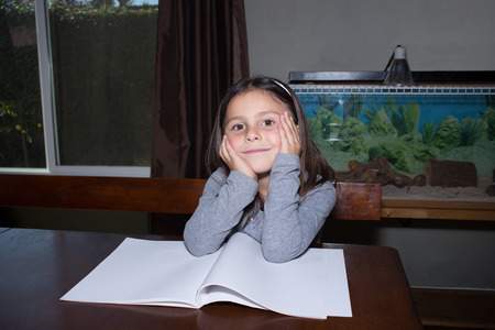 Little Girl Sitting at Table Doing Homework with Blank Book