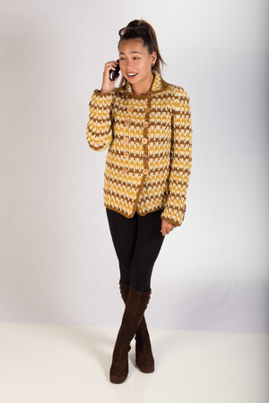 A young lady wearing a knitted sweater and talking on a cell phone while facing the camera
