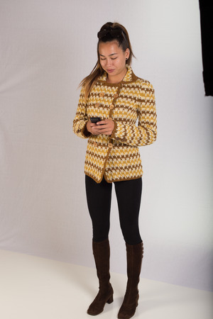 A young lady wearing a knitted sweater and texting on a cell phone while facing the camera  The shot is full body