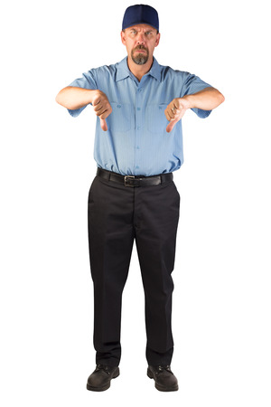 A blue collar worker standing, facing the camera with thumbs down in disapproval