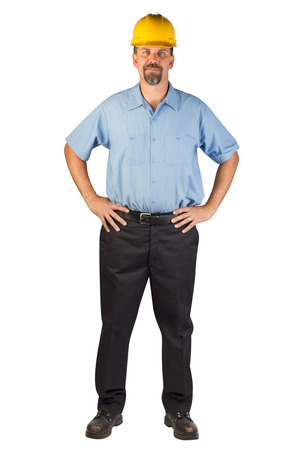 A blue collar worker standing, facing at an angle, strong with hands on hips   Stock Photo