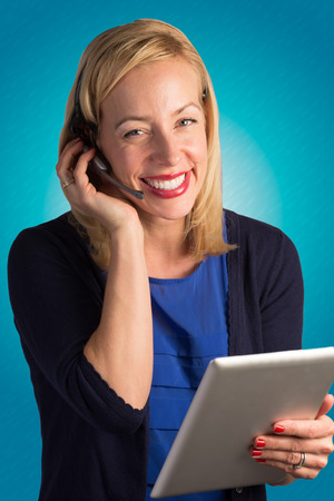 A blonde customer service representative is talking with someone while holding a tablet and looking at the camera  Stock Photo