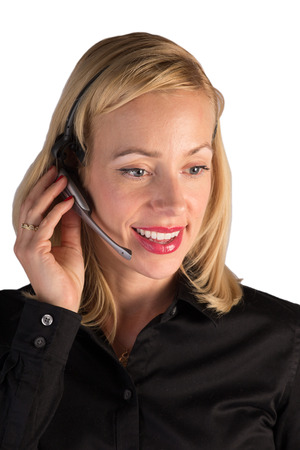 A customer service representative helping a customer on the phone  She is wearing a hands free head set to speak while she types on the computer  Stock Photo
