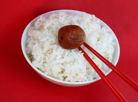Bowl of white rice with ume and chopsticks on red background