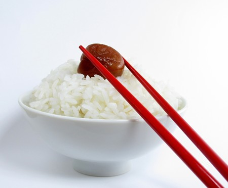 Bowl of white rice with ume and chopsticks on white background Stock Photo
