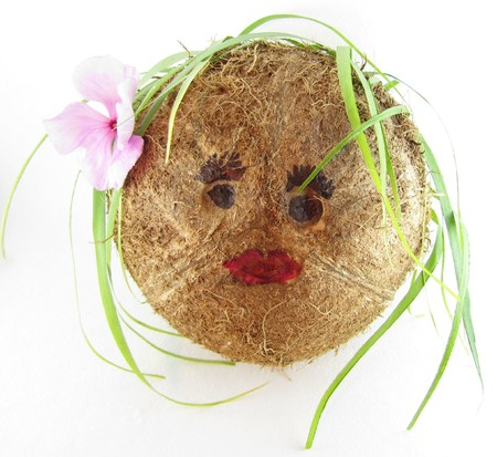 Coconut girl who has tea leaf strips for hair with red lips and a flower behind her ear Stock Photo