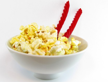 whimsey: rice bowl filled with popcorn instead of rice - and two licorice sticks instead of chopsticks Stock Photo
