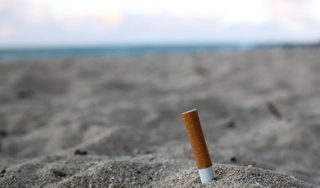 a cigarette butt stuck in sand at a beach with ocean in the background Stock Photo - 7280117