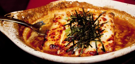 Plate of baked mochi au gratin topped with chopped nori seaweed