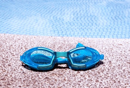 pair of blue goggles by the pool side - horizontal