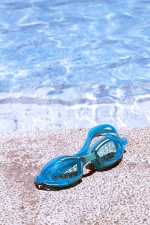 pair of blue goggles by the pool side - vertical