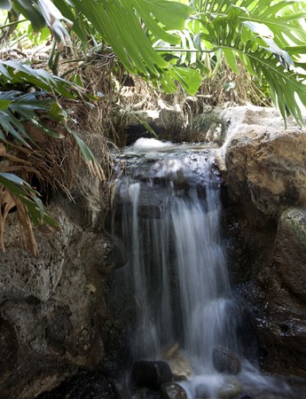 Flowing waterfall in a tropical setting with water and lava rocks
