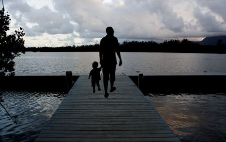 father and son walking on a pier at dusk