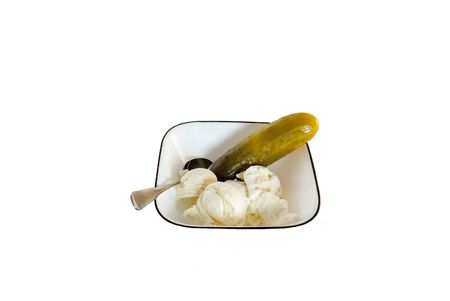 Single pickle and ice cream in a bowl with a spoon isolated on a white background