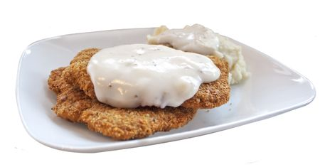 chicken fried steak patties with mashed potatoes and gravy on a white plate isolated on a white background
