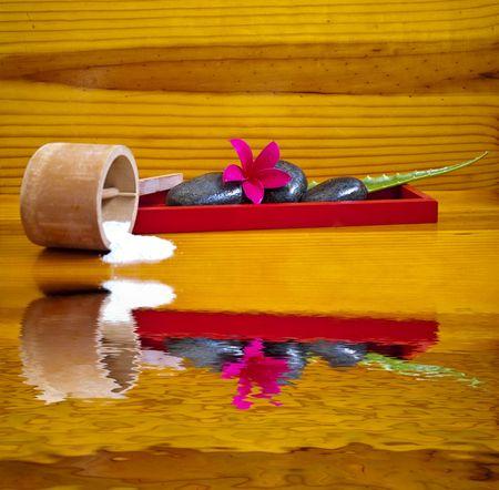 Asian spa setting with massage stones, bath salts, plumeria flower and aloe vera plant stalks photo