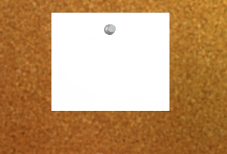 white note with a push pin stuck to a cork board with depth of field