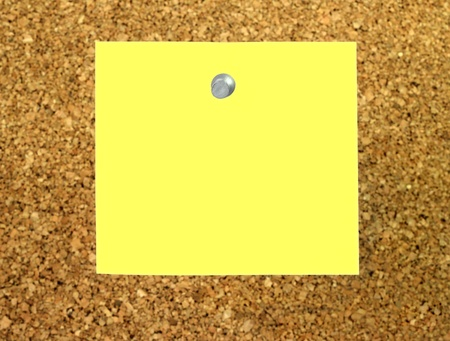 paper pin: yellow note with a push pin stuck to a cork board Stock Photo