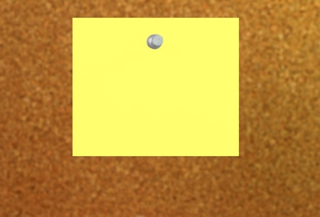 yellow note with a push pin stuck to a cork board with depth of field