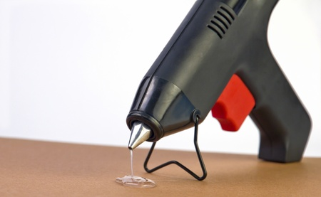 a hot glue gun with glue dripping out of nozzle Stok Fotoğraf