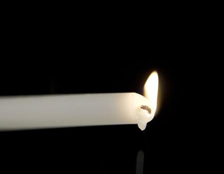 horizontal candle burning on a black background Stock Photo