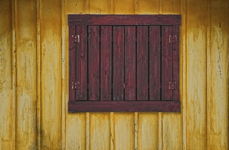 an aged reddish closed window with yellow plank walls Stock Photo - 10996058