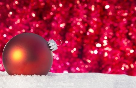 red christmas ornament in snow with sparkly red tinsel in background Stock Photo