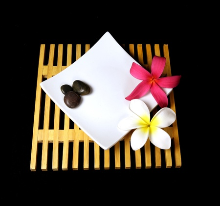 plumeria flowers and stones on a white plate and wooden trivet with a black background