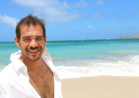 close up of young handsome man smiling standing by beach