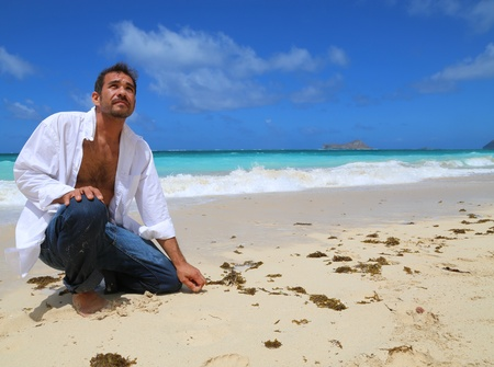 Young handsome man kneeling by the beach looking up at sky