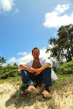 young male smiling and sitting on a hill by the beach