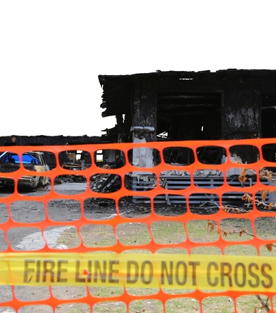 House and car burned in a fire (focus on the house) behind a orange fence, the background has been removed and is isolated on white